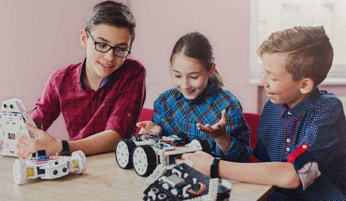 Foto de tres niños montando un robot educativo