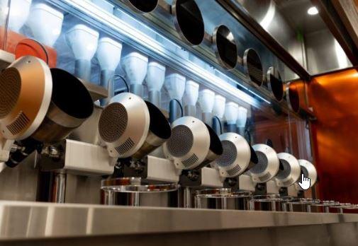 Robots cocineros con forma de sartener wok y ollas en el restaurante Spyce de Boston